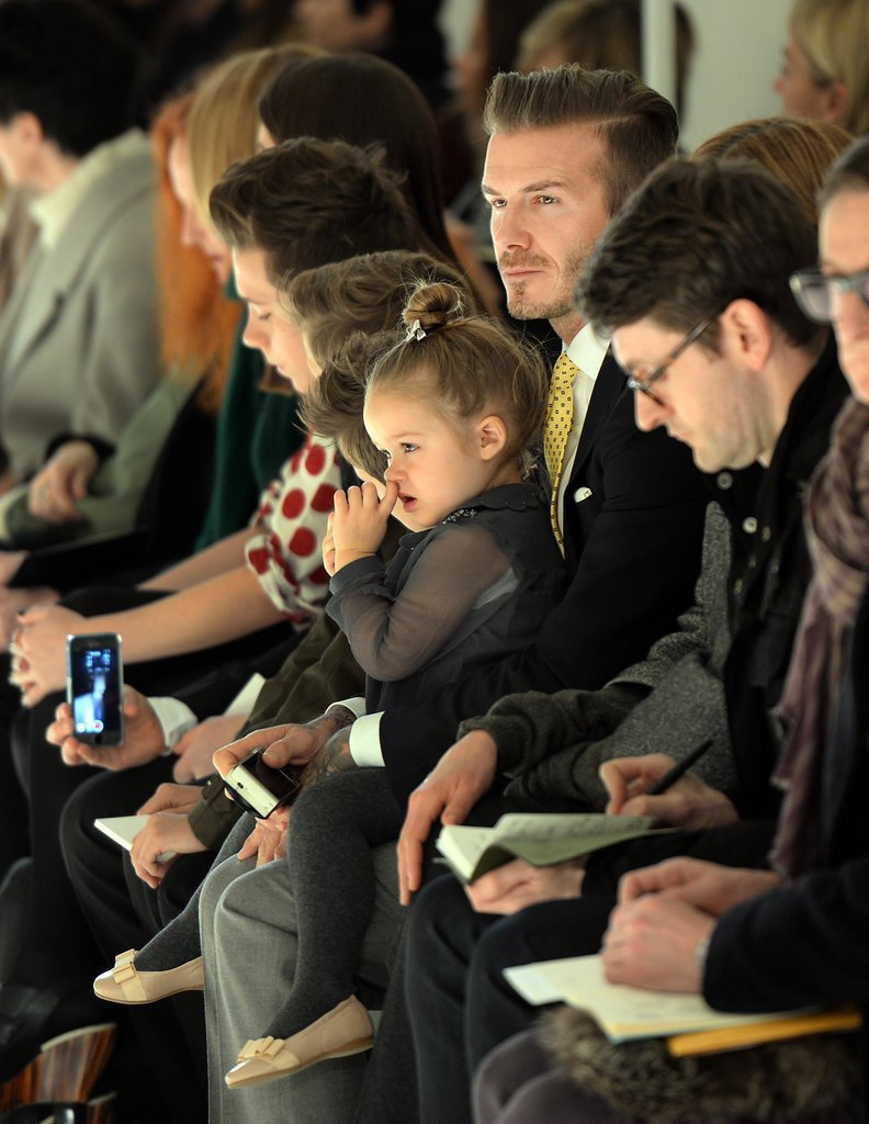 David Beckham held his daughter, Harper, on his lap as they watched Victoria's show at New York Fashion Week on Sunday.