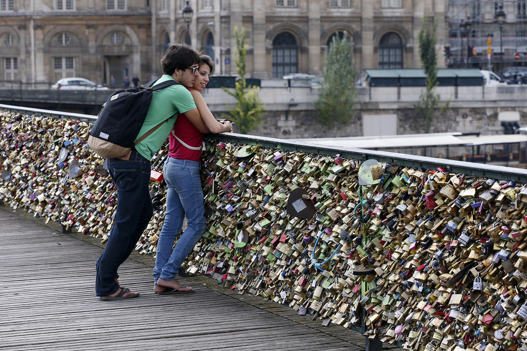 A couple gets romantic next to the love lock-covered Le Pont Des Arts bridge.