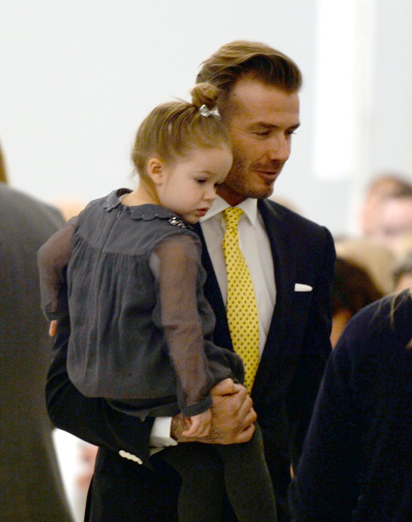 David Beckham held his daughter, Harper, at his wife's show on Sunday.