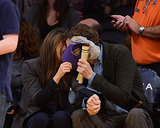 Mila Kunis and Ashton Kutcher kissed behind a hat at a Lakers game in LA.