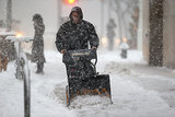 A doorman removed snow from the slushy NYC sidewalk.