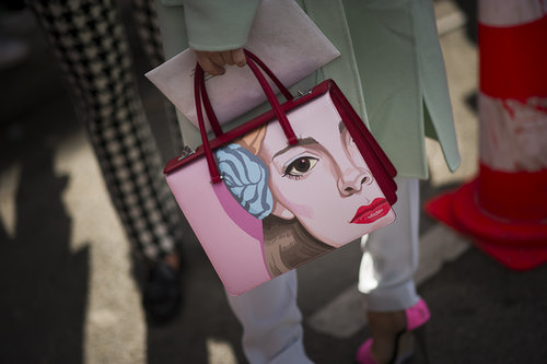 How do you really make a statement with your accessories? With a face-painted Prada bag.