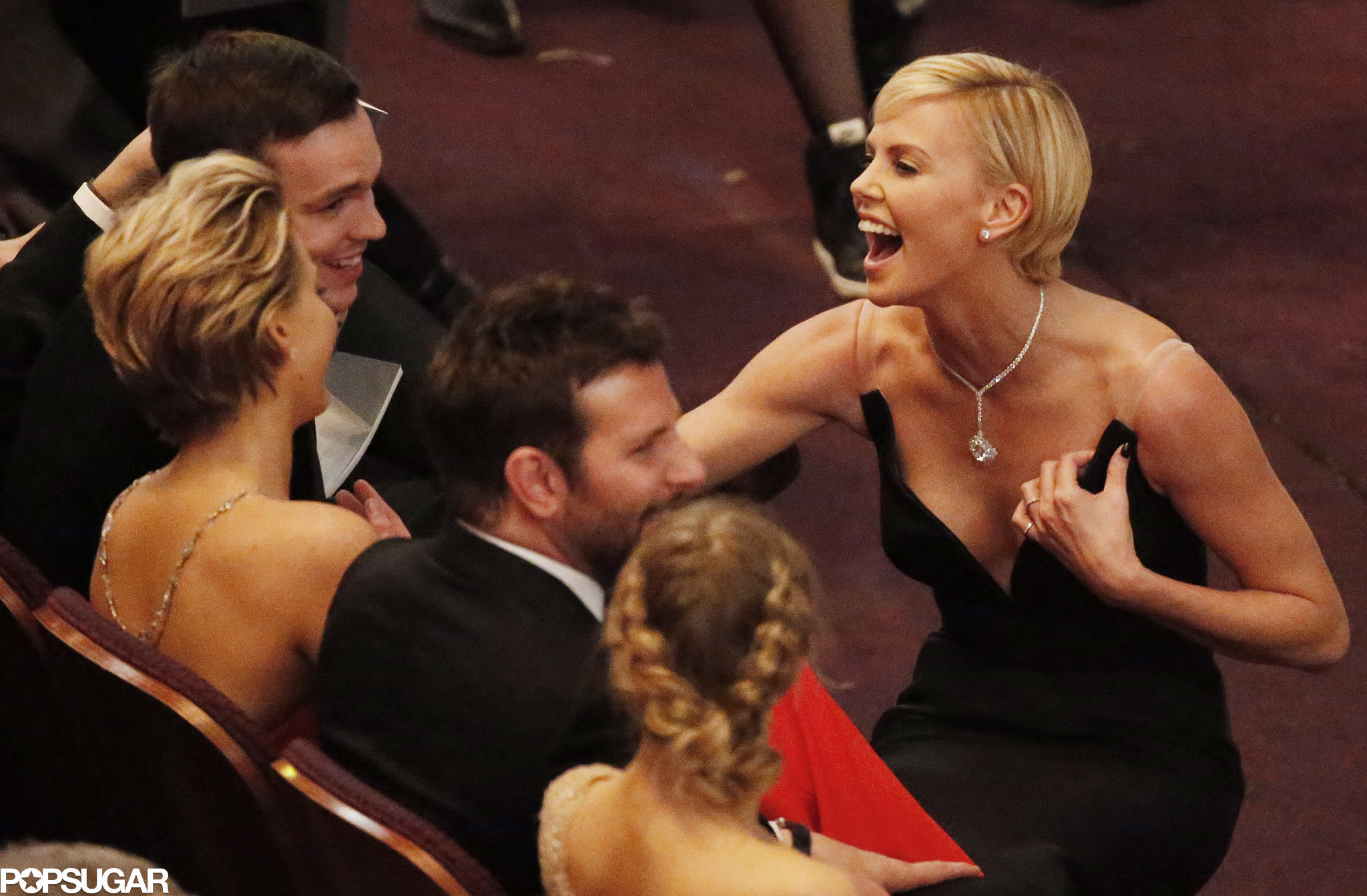 Charlize Theron cracked up while chatting with Jennifer Lawrence and her boyfriend, Nicholas Hoult, in the front row.