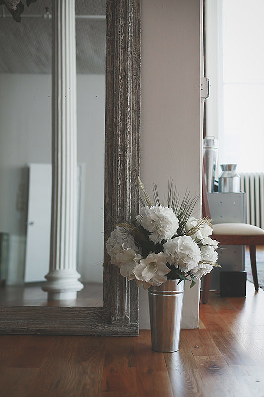 A large, floor-length mirror reflects more of the natural light (not to mention that stunning Corinthian column!).  Photo by Chellis Michael Photography