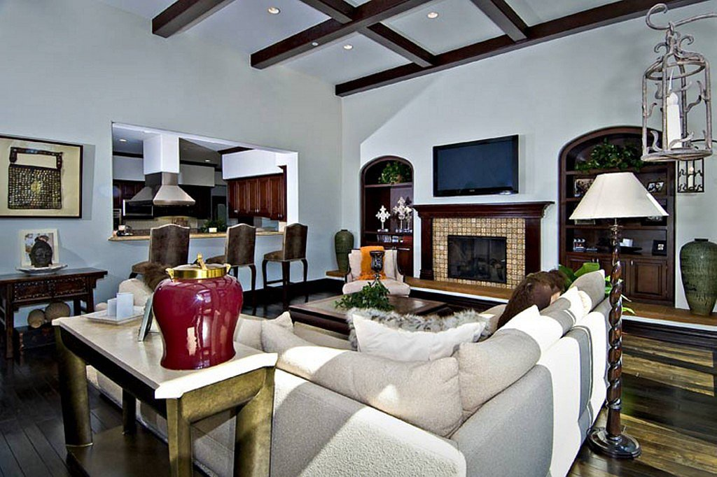 The family room's wood-beam ceilings and tiled fireplace fit within the home's Spanish-styled architecture.  Source: Trulia