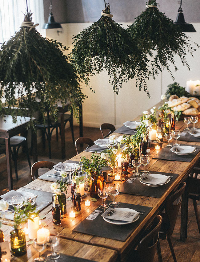 To bring the outdoors in, use greenery to cover industrial lights. The overall look lends to an urban-meets-rural-inspired reception. Photo by Giuli & Giordi via Green Wedding Shoes