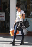 For an afternoon in LA, Alessandra Ambrosio went supercasual, knotting a plaid shirt around her waist, wearing flat black boots, and carrying a Mansur Gavriel bucket bag.