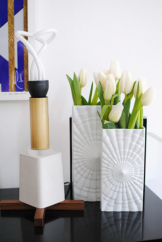 Alexis's table lamp and vases look just as artful as the colorful piece hanging on her wall.   Source: Homepolish