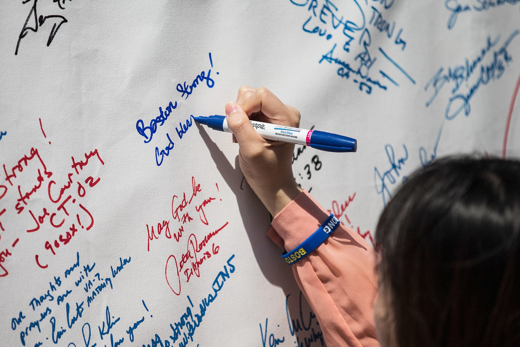 People wrote tributes on a memorial sign during Boston Medical Center's commemoration of the bombing's one-year anniversary.