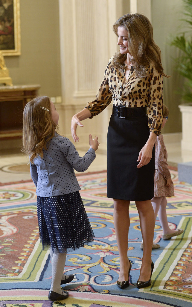 She shook hands with a little girl while visiting with people at Zarzuela Palace in October 2013.
