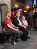 Domhnall Gleeson, Robbie Coltrane, and Warwick Davis listened to a question during their panel.