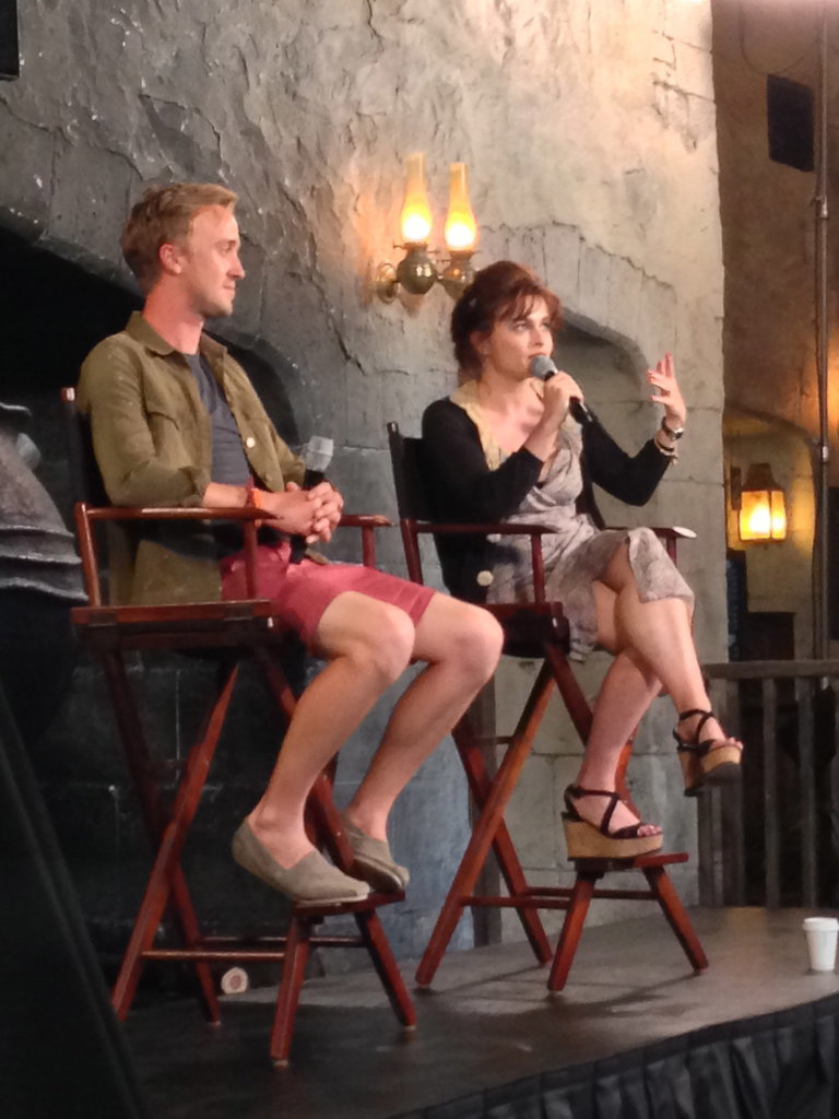 "Tom Felton and Helena Bonham Carter, who play villains Draco Malfoy and Bellatrix Lestrange, answered questions during a panel. The two are far from villainous in their real lives. In fact, Helena shared that her two children (with partner Tim Burton), Billy and Nell, were ""enchanted"" with Diagon Alley. She added that Nell, who's 6, just started reading the first book."