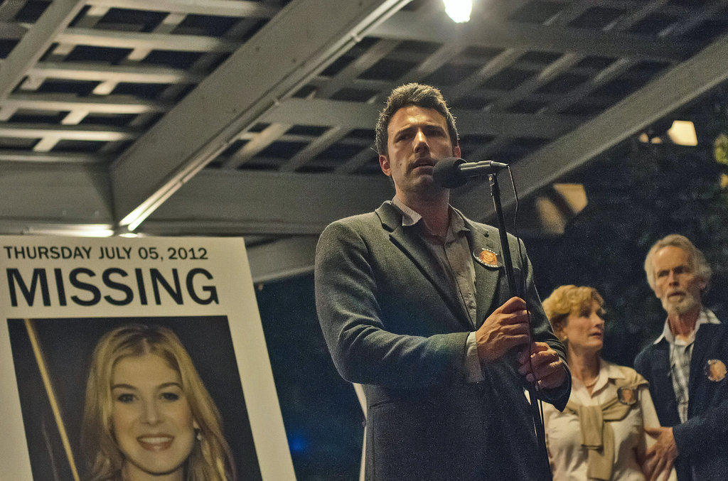 Nick looks concerned while speaking . . . But is it concern for him or for Amy (Rosamund Pike)?
