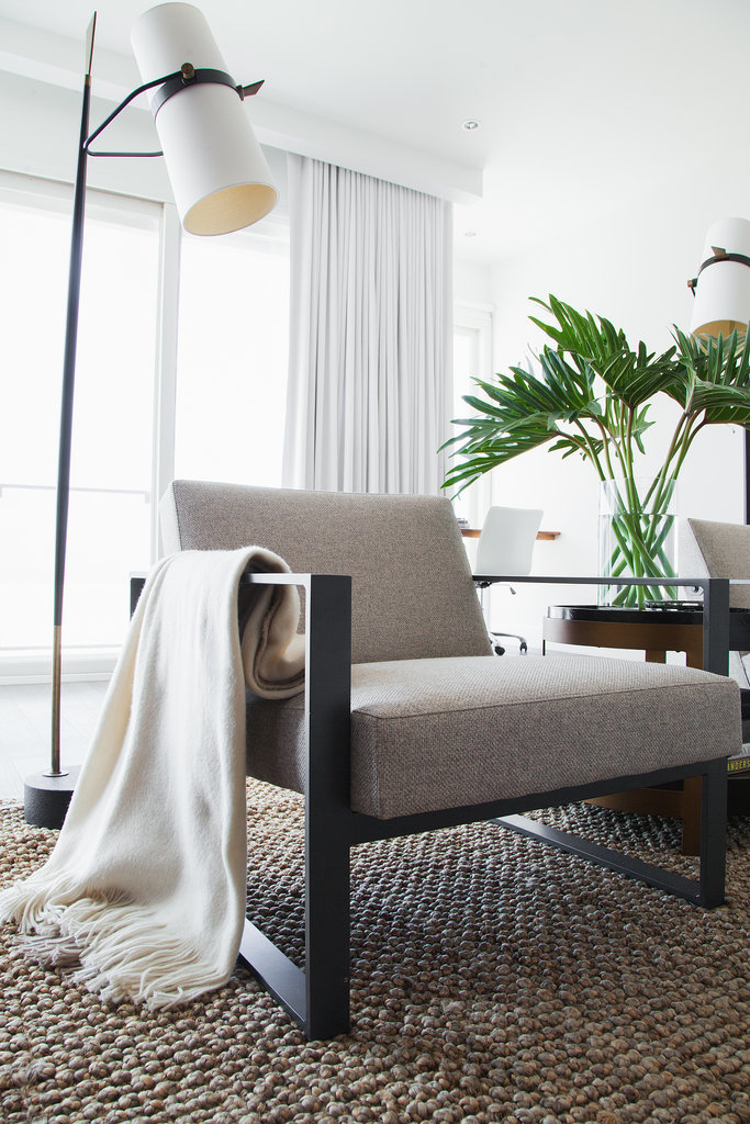 Natural textures such as a jute rug and palm leaves reference the beach landscape just outside. White drapes frame the view without distracting from it.   Photo by Tessa Neustadt via Homepolish