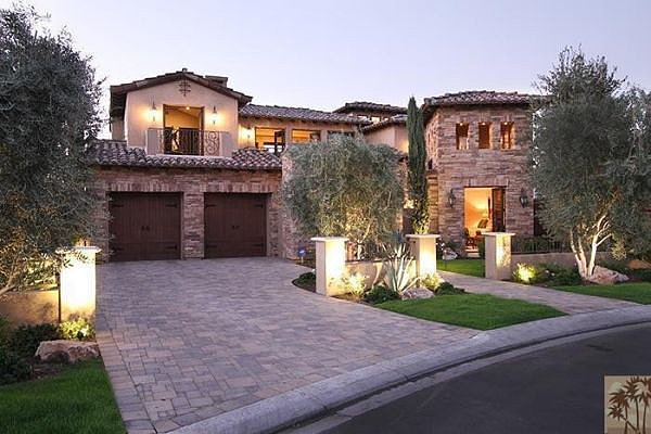 The stone exterior looks even more grand thanks to manicured landscaping and lighting. Source: Realtor.com