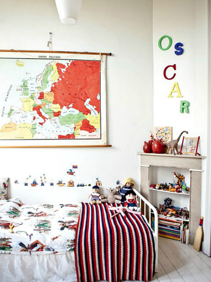 Oscar's room as shown in Milk Magazine: Dif­fer­ent sized, mul­ti­col­ored let­ters spell out Oscar's name loud and clear in this beau­ti­ful Brussels-based bedroom. I love the color palette cre­ated by Oscar's par­ents, French pho­tog­ra­pher Vin­cent and Jus­tine Glan­field (of Cot­ton & Milk fame). The old-school map and let­ter­ing have a uni­fy­ing effect on this sim­ple space, packed with a jum­ble of toys, pat­terns, and vin­tage acces­sories. For a sim­i­lar look, check out spe­cial­ist stores like Kidimo, or scour your local flea mar­kets until you find your unique com­bi­na­tion of letters!