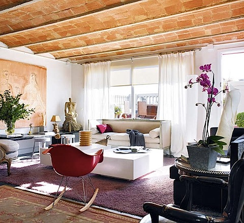 I love the unexpected red pop of this Eames rocker against the neutral colors in this living room.  Source