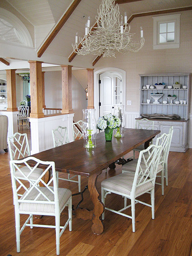 Painted white, a busy branch chandelier floats beautifully in this dining room. Source