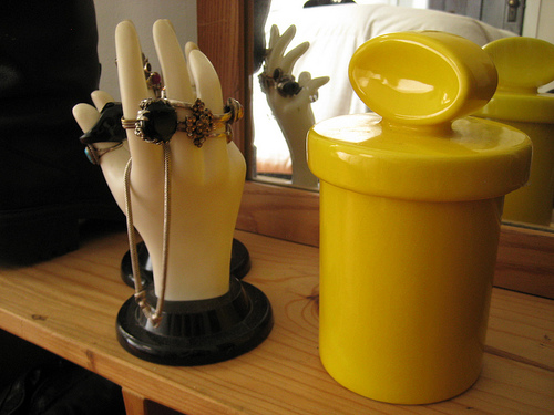 Try using cute containers to stack bangle bracelets. A hand mold can work wonders on your blingy costume rings. Source:  Flickr User backgarage