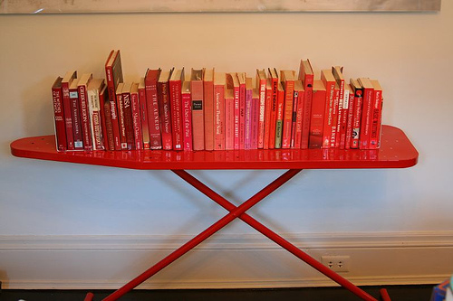 "Flickr user ninahale notes, ""We took our ironing board to a powder coater to paint red and we're using it as a bookshelf in the dining room. (And [we] put red books on it)."" Source:  Flickr User ninahale"