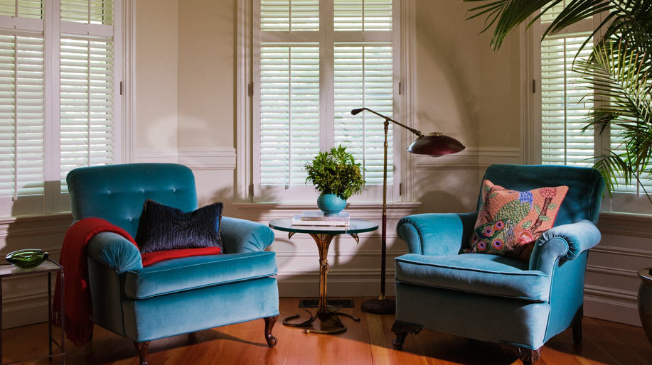 If you can't commit to a cool wall color, use cool colors in your furniture and accents instead. These velvet tufted turquoise chairs add a great pop of color to this room, and the blue vase complements them well.  Source
