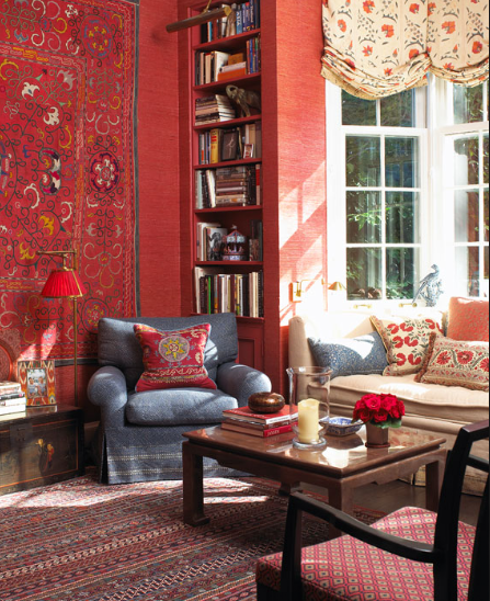 An antique kilim, hung on the wall, matches the red textured wallpaper behind it. This entire room is full of pattern, color, and comfort. Source