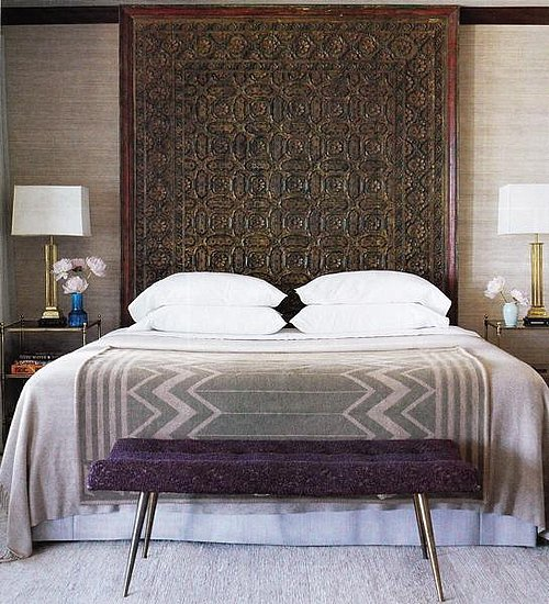 An intricate brown headboard offers a grounding influence in this eclectic, textured bedroom. Source