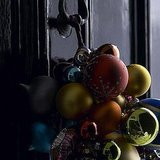 Hang a bunch of ornaments from your door knocker to give guests a festive welcome. Source