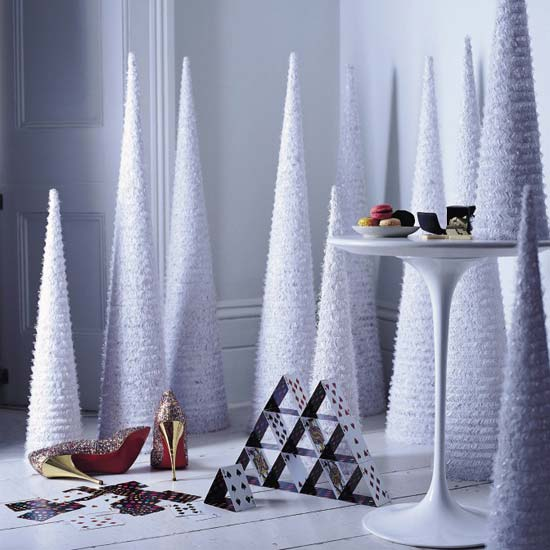 Wrap cones with tinsel at varying heights to create a chic, minimalist holiday display. Source