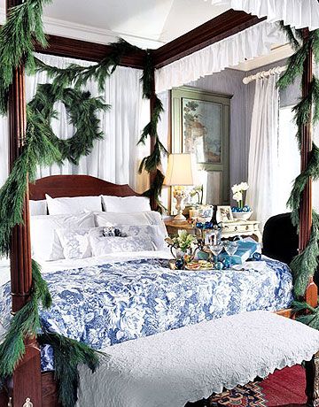 A four-poster bed, bedecked with pine garlands, is so cozy and seasonal. Source
