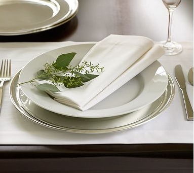 If you prefer a minimal, Winter white table setting at your holiday fiesta, you can give it a little flair by placing a cut of greenery on top of each place setting.