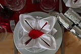 Fold your napkins into a rose shape and top them with a paper leaf to make your place settings the focal point. Source: Flickr User dps