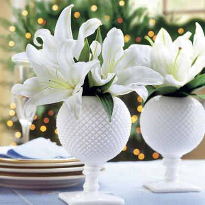 Lilies get holiday-ready when displayed in classic milk glass. Try adding sprigs of white pine to add to the holiday effect.  Source
