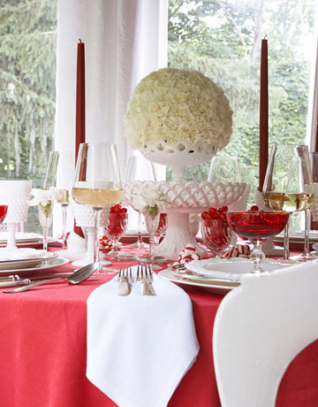 Eddie Ross created a dramatic red and white holiday table setting for House Beautiful. I love his use of carnations as a spherical centerpiece.  Source