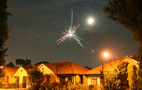 A residential neighborhood in Melbourne glows under street lights and a single firework. Source:  Flickr User Shiny Things