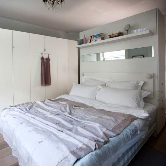 In this bedroom, the wall of white cupboards serves as extra closet space. If you don't have closet space built into your bedroom, consider adding a wall of cupboards similar to this one. Source