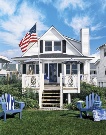This beach house's stark white exterior makes the flag stand out in this photo, while the pastel blue Adirondack chairs soften the overall impression.  Source