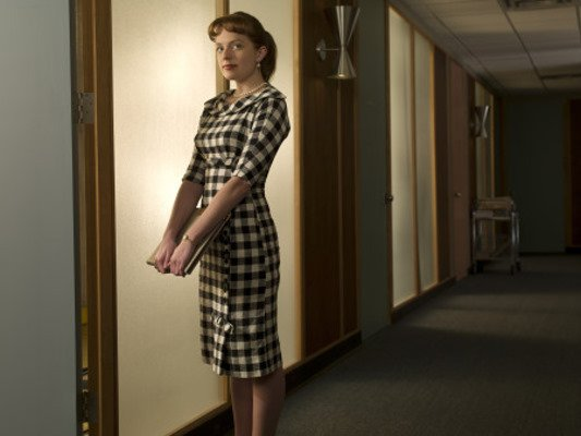 Junior Copywriter Peggy Olson is breaking the glass ceiling at Sterling Cooper, as the only female copywriter at the company. Her stylish outfits fit right in with the chic translucent windows and atomic-age silver sconces. Source