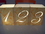 Intimate Weddings has a tutorial on creating these illuminated table numbers.