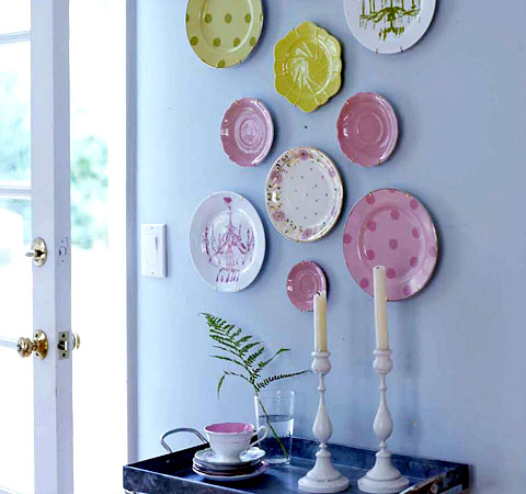 Choosing unusual colors, such as pinks and yellows, can create a unique display. Hanging your plates above a piece of furniture, such as this bar cart, helps to highlight the plates.  Source