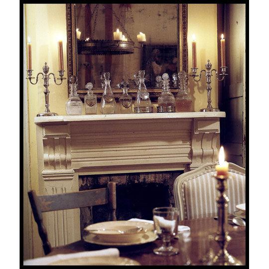 Candles in candlesticks on the mantel, the table and in an overhead chandelier, create a gorgeously warm atmosphere in this dining room. The mirror above the mantel wonderfully reflects and amps up the light from the candles.  Source