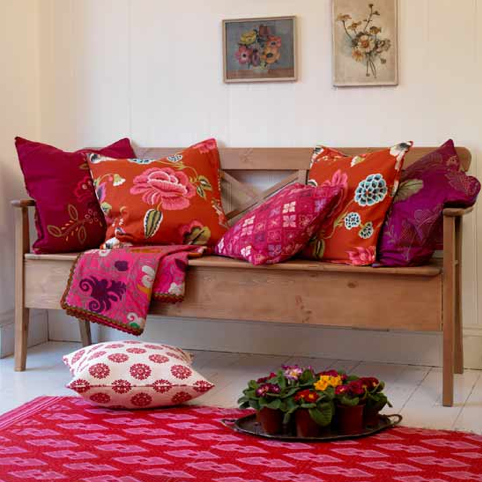 Create a vibrant, bohemian nook with brightly patterned throw pillows and an equally eclectic throw. Source