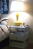 Her sunny yellow table lamp and nightstand both have Hollywood Regency style.