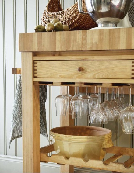 A simple Ikea butcher block cabinet gets doubly useful when combined with wine glass storage beneath the pull-out drawer. Source