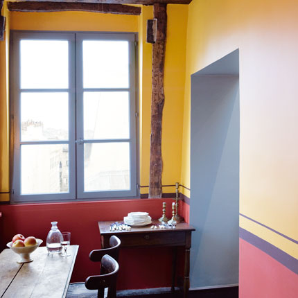 A medium-toned hue of yellow like this one could look a bit too dated and yolky, but using a painted baseboard of darker colors balances it. The stripes add flair. Source