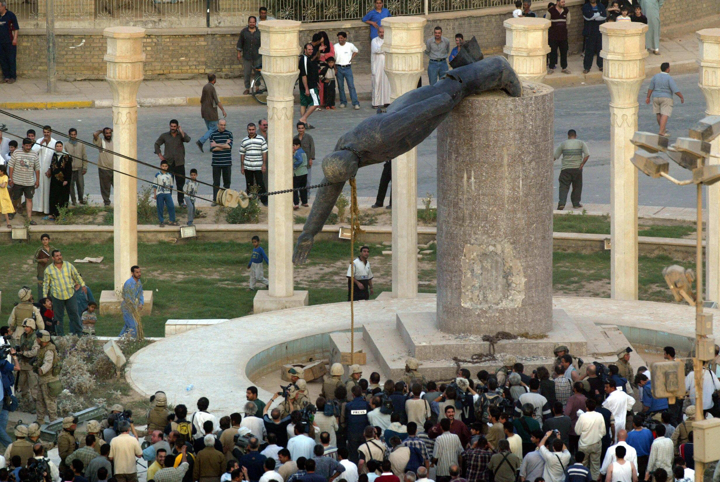 Iraqis watch a statue of Iraqi President Saddam Hussein falling in Baghdad. April 9, 2003.