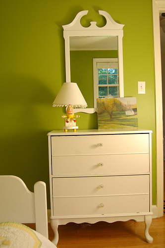 White furniture contrasts beautifully with the apple-green walls.
