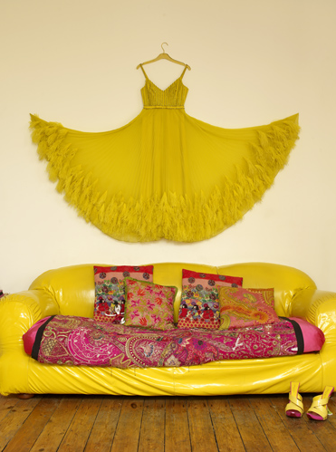 """Also in Bazaar Style, it reads, """"Made by the fashion-designer owner of this house, this canary-yellow gown makes a show-stopping piece of wall art. Combined with a matching vinyl-covered sofa and patterned pillows, it creates an uncompromisingly bright scheme."""" Of course, the latest trend is propagated by a fashion designer. Source"""
