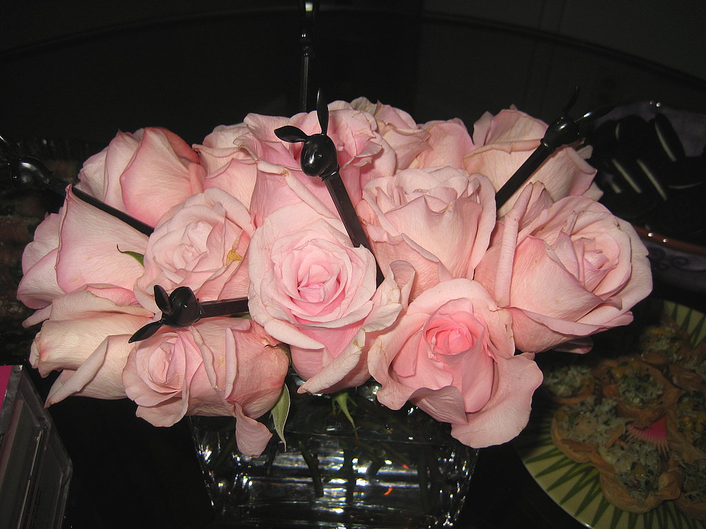 The floral arrangements were pale pink roses in clear glass vases. Black Playboy Bunny drink stirrers adde