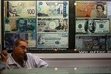 A man talks on the phone at a money exchange counter.
